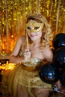 Schönes junges mädchenmodell blondes lächeln bedeckt ihr gesicht mit einer karnevalsmaske in einem eleganten goldkleid mit einem reifenhörnerhintergrund von lotusbändern mit girlanden, die auf dem boden sitzen.