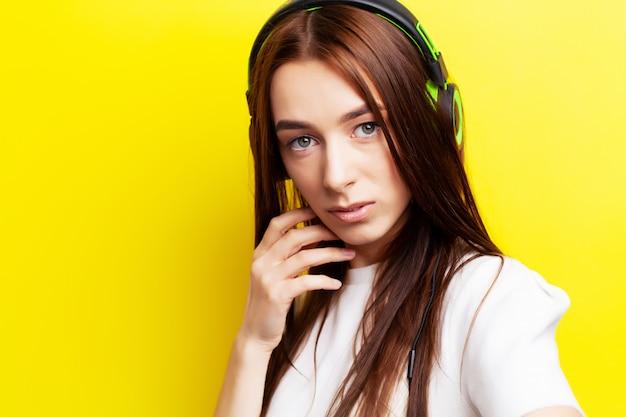 Schönes junges mädchenmodell hört musik in kopfhörern auf gelb