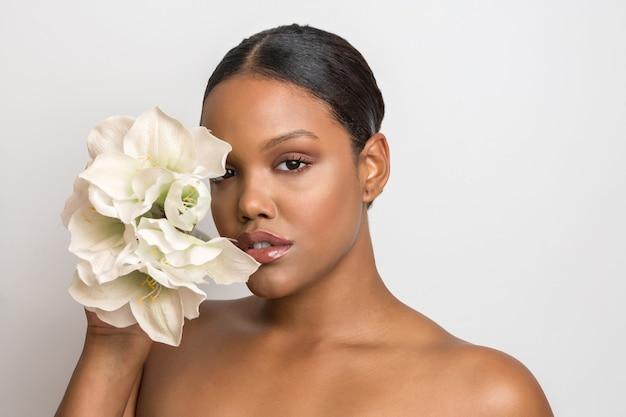 Schönes junges model mit elegantem natur-make-up, das die hälfte ihres gesichts mit zarten weißen blüten bedeckt