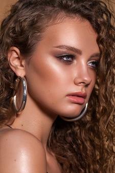 Schönes junges model mit professionellem make-up, lockigem haar, nasser, gebräunter haut