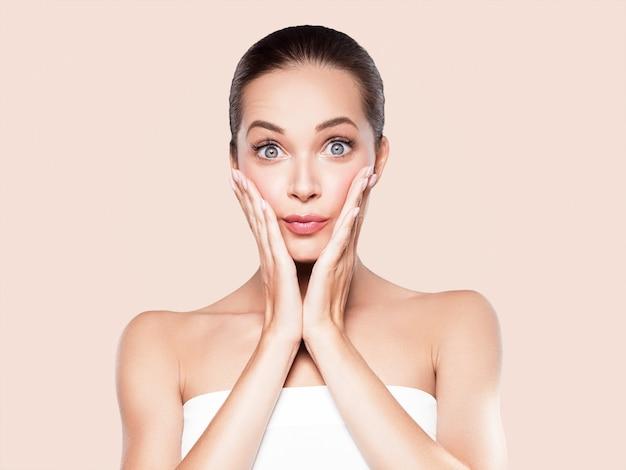 Schönes junges modell des frauenschönheitsgesichtes der gesunden haut natürliches make-up mit den händen. auf beige.