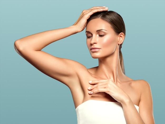 Schönes junges modell des frauenschönheitsgesichtes der gesunden haut natürliches make-up mit den händen. auf blau.