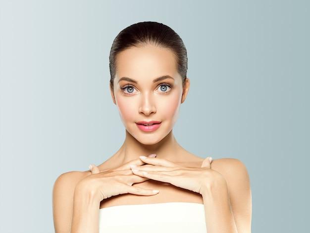 Schönes junges modell des frauenschönheitsgesichtes der gesunden haut natürliches make-up mit den händen. auf grau.