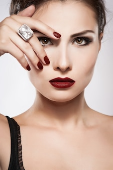 Schönes junges modell mit den roten lippen und roter maniküre
