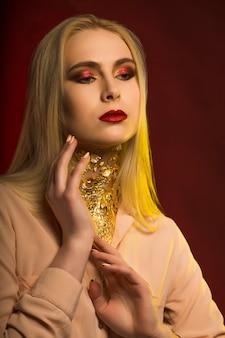 Schönes junges modell mit hellem make-up und goldener folie. rotes und gelbes studiolicht