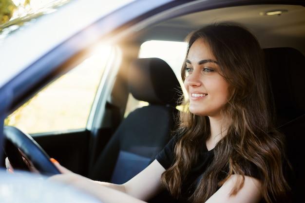 Schönes junges modernes mädchen, das ein auto am sonnigen sommertag fährt. fahrerin allein im auto, nahaufnahme, sonne auf dem hintergrund.