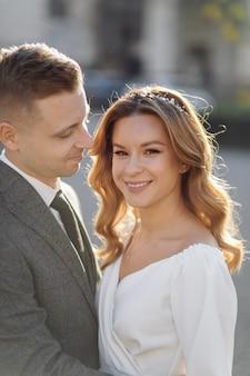 Schönes junges modisches stilvolles paar, das auf der straße in der stadt geht