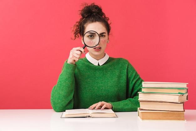 Schönes junges nerd-studentenmädchen, das isoliert am tisch sitzt, mit büchern studiert und lupe hält