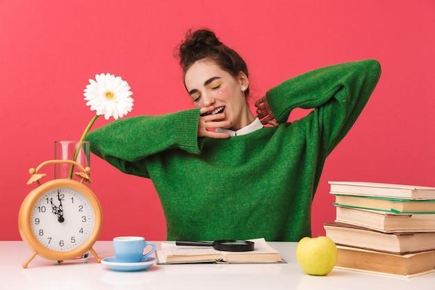 Schönes junges nerd-studentenmädchen, das isoliert am tisch sitzt und mit büchern studiert,