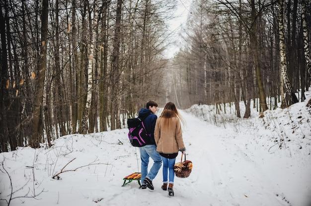 Schönes junges paar auf einem rückweg, der schlitten zieht, wintertag. schöne ferien. frohe weihnachten und ein gutes neues jahr konzept.