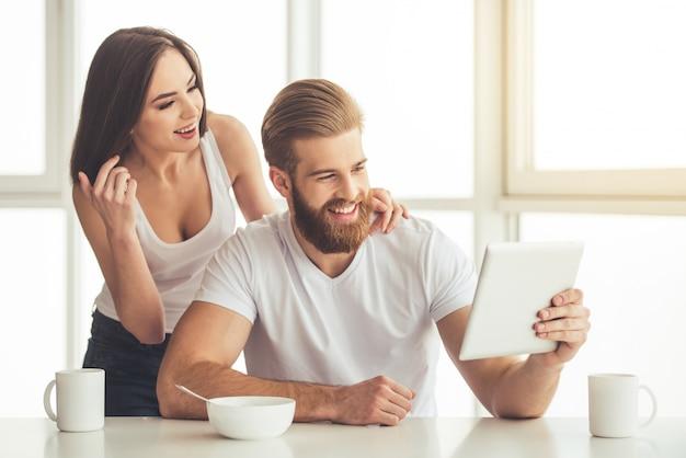 Schönes junges paar benutzt eine digitale tablette