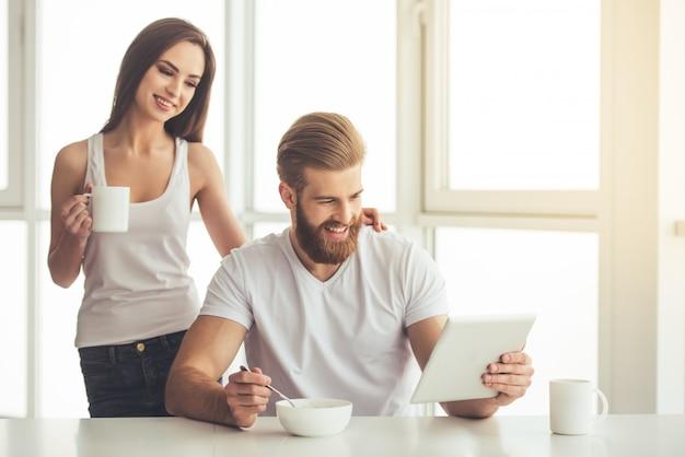 Schönes junges paar benutzt eine digitale tablette.