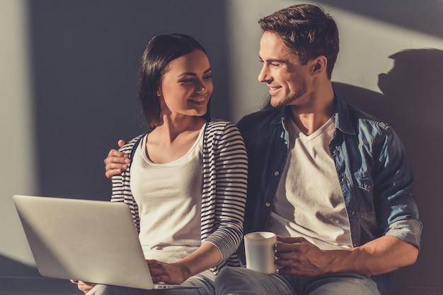 Schönes junges paar benutzt einen laptop