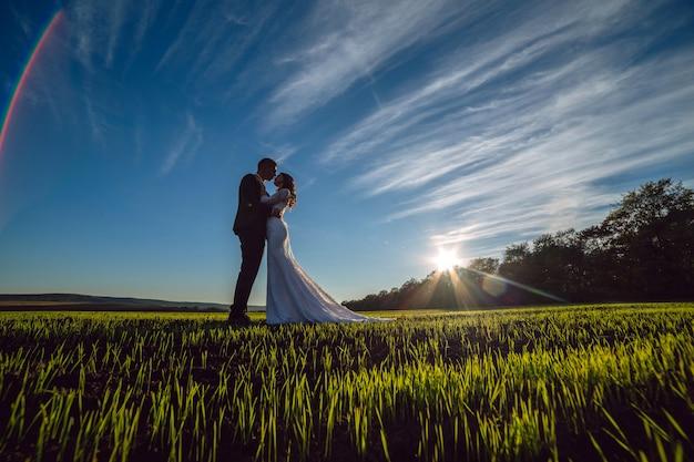 Schönes junges paar, braut und bräutigam, die an einem sonnigen tag im freien gehen