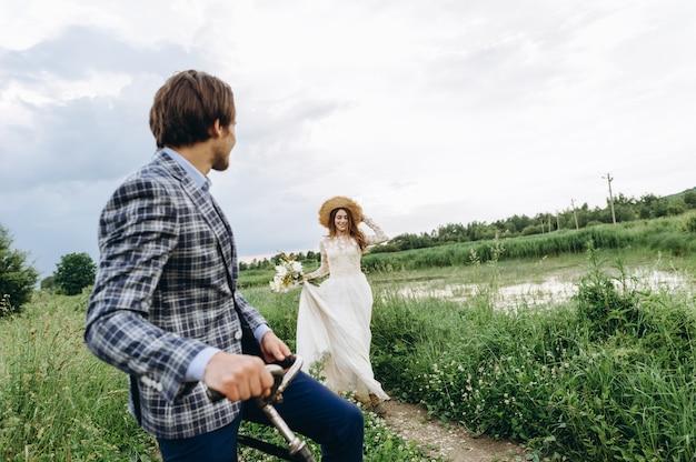 Schönes junges paar braut und bräutigam, die in einem feld mit einem fahrrad gehen