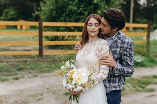 Schönes junges paar braut und bräutigam, die nahe dem hölzernen zaun gehen
