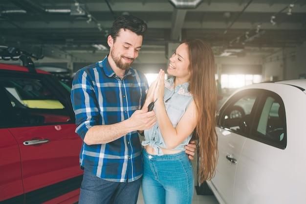Schönes junges paar, das am autohaus steht und das auto wählt, um zu kaufen.