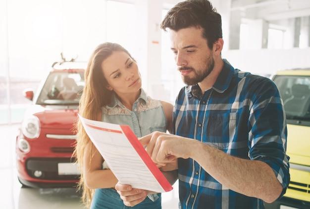 Schönes junges paar, das am autohaus steht und das auto wählt, um zu kaufen