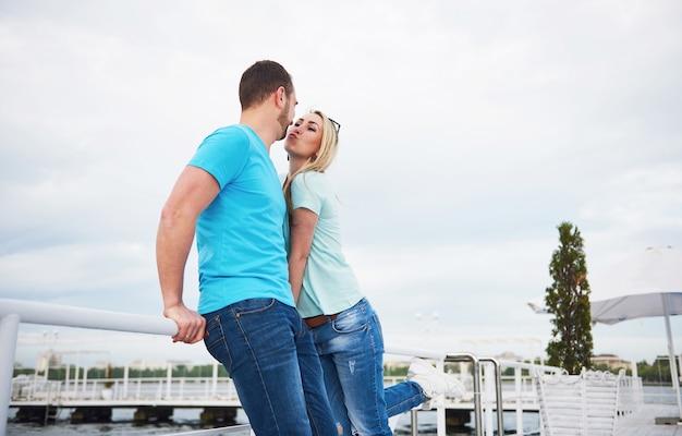 Schönes junges paar, das auf einem pier nahe wasser küsst.