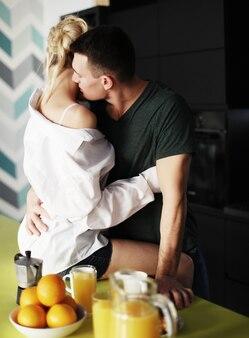Schönes junges paar, das auf einer küche zu hause steht und sich umarmt