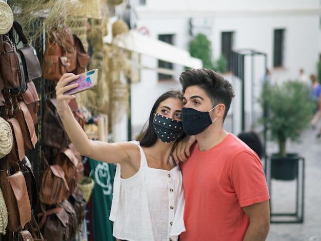 Schönes junges paar, das bei einem romantischen date medizinische masken trägt - die neue normalität aufgrund von covid-19