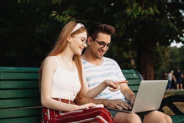 Schönes junges paar, das den bildschirm ihres laptops lächelnd betrachtet, während mädchen mit roten haaren mit dem finger im freien auf der bank zeigt.