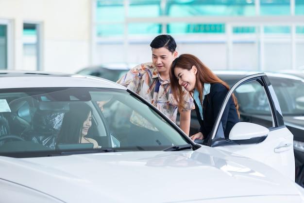 Schönes junges paar, das ein auto im autohaus wählt, das mit dem salonmanager in einem neuen auto beim professionellen verkäufer des autohauses spricht, der die autoeigenschaften zeigt, die autos kaufen.