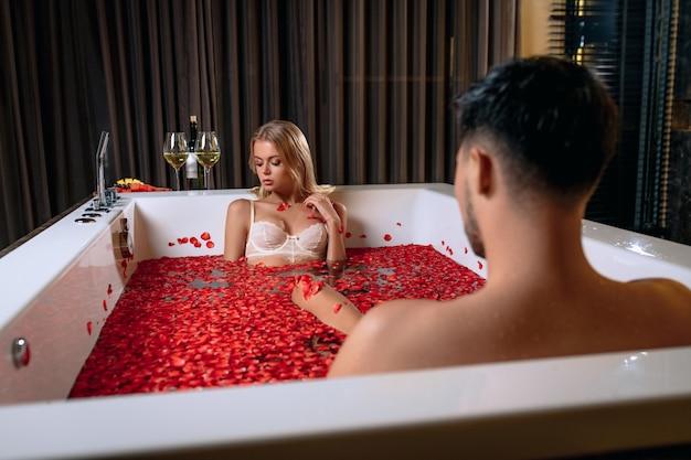 Schönes junges paar, das ein bad mit rosenblättern genießt