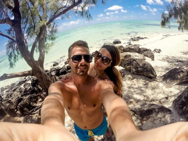Schönes junges paar, das ein schönes junges paar nimmt, das ein selfie am strand macht und ihre flitterwochen genießt.
