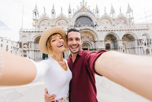 Schönes junges paar, das ein selfie in venedig, italien auf piazza san marco nimmt. glückliche frau und mann in der liebe, die zusammen reisen.
