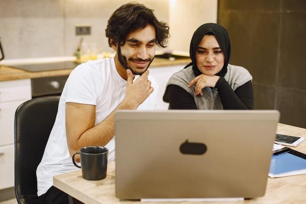 Schönes junges paar, das einen laptop verwendet, in ein notizbuch schreibt und zu hause in einer küche sitzt. arabisches mädchen mit schwarzem hidjab.