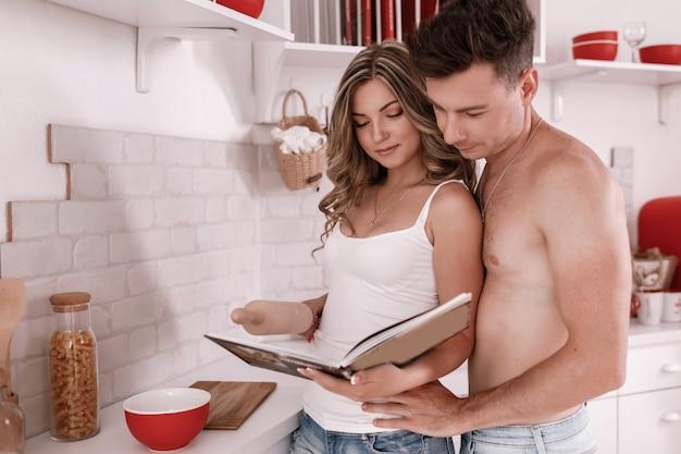 Schönes junges paar, das gesundes essen in der häuslichen küche kocht. sie lesen rezepte aus dem kochbuch. paar liest rezeptbuch. selektiver fokus