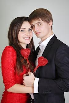 Schönes junges paar, das herzen auf einem stock hält