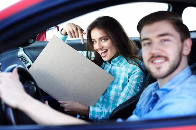 Schönes junges paar, das im auto sitzt und kamera betrachtet, lächelnd, glücklich, auf modell zeigt, raum kopiert, modell verspottet.