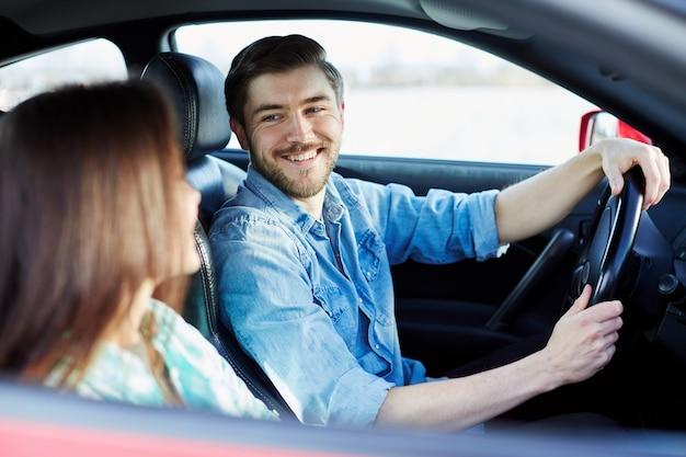 Schönes junges paar, das im automobil sitzt und einander ansieht, lächelnd, glücklich.