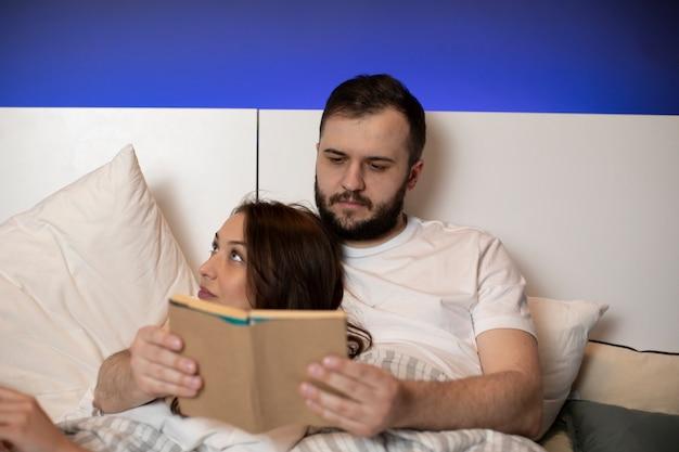 Schönes junges paar, das im bett liegt und zeit zusammen vor dem schlafengehen verbringt