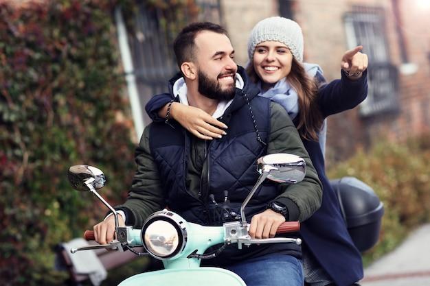 Schönes junges paar, das im herbst beim rollerfahren in der stadt lächelt
