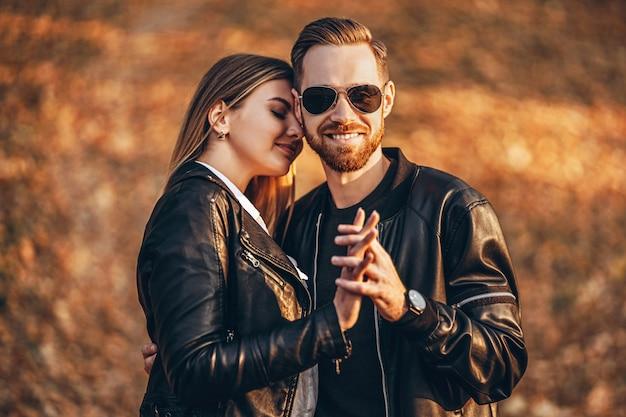 Schönes junges paar, das im herbstpark an einem sonnigen tag geht. sie umarmen sich und lächeln, genießen einen spaziergang