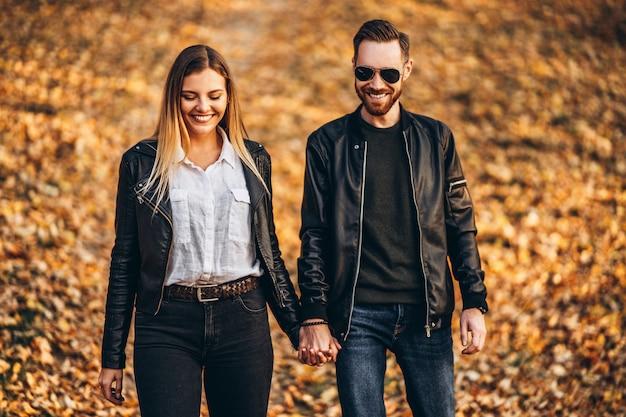 Schönes junges paar, das im herbstpark an einem sonnigen tag geht.