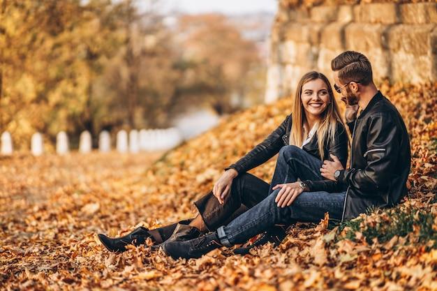 Schönes junges paar, das im herbstpark an einem sonnigen tag geht