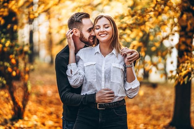 Schönes junges paar, das im herbstpark an einem sonnigen tag geht Premium Fotos