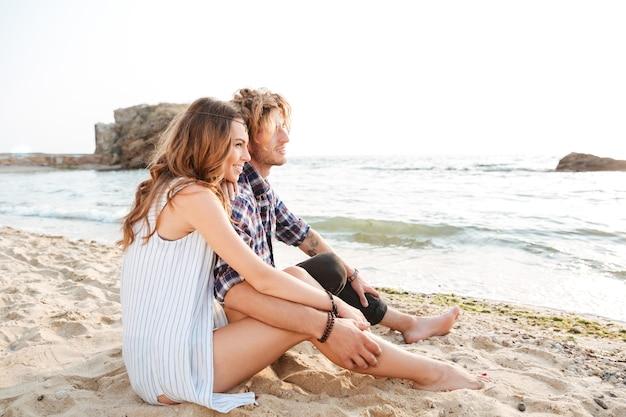 Schönes junges paar, das im sommer am strand sitzt
