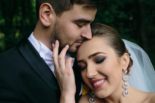 Schönes junges paar, das im wald aus engem winkel aufwirft