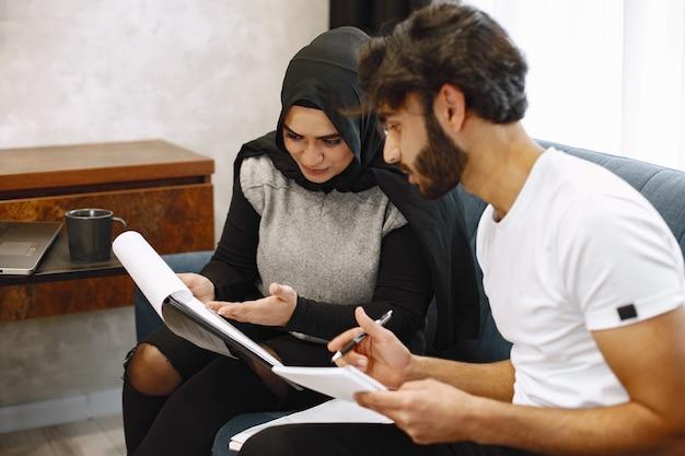Schönes junges paar, das in ein notizbuch schreibt und zu hause auf couck sitzt. arabisches mädchen mit schwarzem hidjab.
