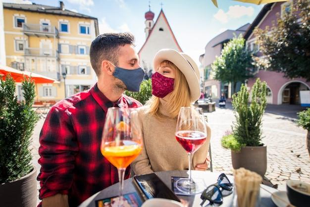 Schönes junges paar, das in einem barrestaurant sitzt und etwas trinkt zwei liebhaber, die draußen datieren