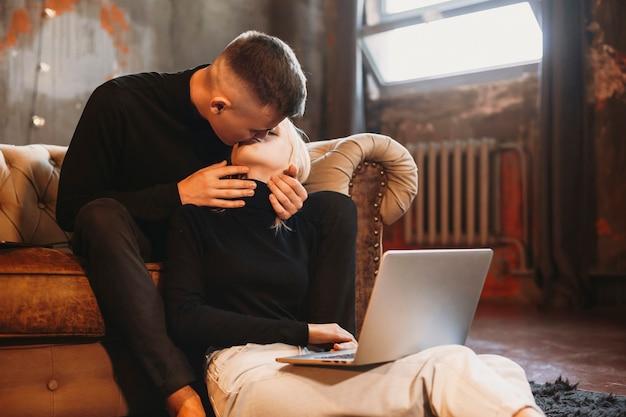 Schönes junges paar, das küsst, während mann auf einem sofa und mädchen auf dem boden sitzt, das zu hause an einem laptop arbeitet.