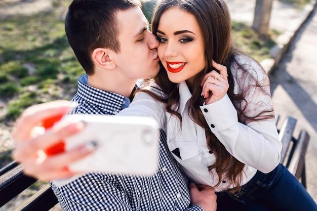 Schönes junges paar, das spaß auf einer bank im park hat