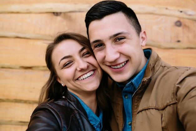 Schönes junges paar, das über holzwand aufwirft