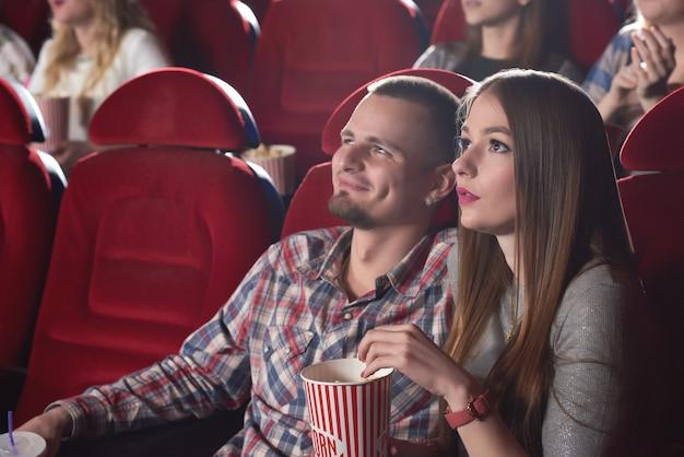 Schönes junges paar, das zusammen einen film während ihrer verabredung im kino sieht