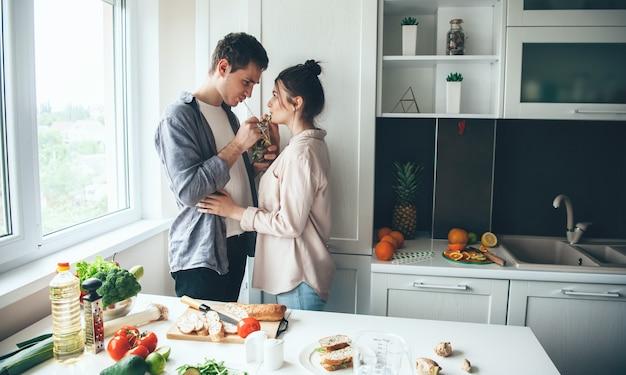 Schönes junges paar, das zusammen mojito trinkt, während abendessen zusammen in der küche vorbereitet wird
